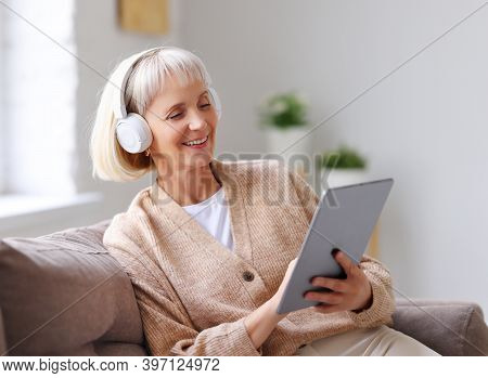 Happy Elderly Female In Headphones Smiling And Browsing Social Media On Tablet While Sitting On Sofa