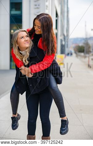 Two Close Woman Friends Having Fun And Piggybacking In City