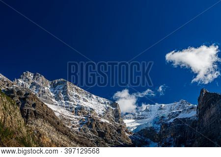 Snow-covered Majestic Mountain Peaks With Dark Blue Sky And Flowing Clouds In The Background. Valley