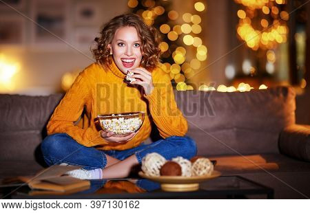Young  Delighted Cheerful Woman Eating Popcorn Laughs And Watches  Christmas Comedy Movie On  Cable