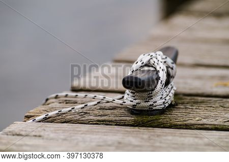 Boat Rope Secured To Cleat On Wooden Boating Dock Or Pier.