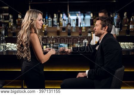 A Young Blonde Woman And A Successful Man Are Talking At The Bar In A Restaurant, Drinking Cocktails