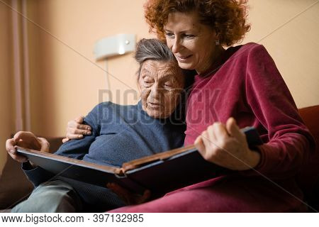 Positive Aged Ladies Looking Album Photos Sitting Sofa At Home, Cheerful Friends. Senior Woman And H