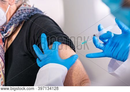 Female Doctor Applying The Coronavirus Vaccine To An Elderly Lady. Antibodies, Immunize Population.