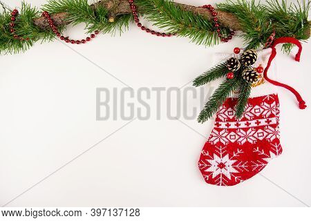Santas Red Stocking Lies Next To A Wooden Ornament With Christmas Cones On A White Background. Chris