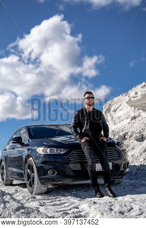 Portrait Of A Stylish Bearded Man In Trendy Sunglasses And Leather Jacket Stands Near Black Car. Fas