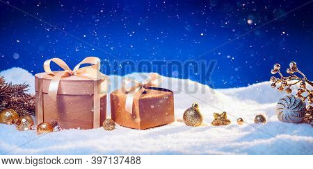 Winter Holidays Background With Eco-friendly Gift Boxes And Golden Christmas Ornaments On Snow.