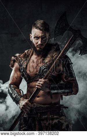Savage And Barbaric Viking Seafarer Holding Two Handed Axe In Dark Foggy Background Staring At Camer