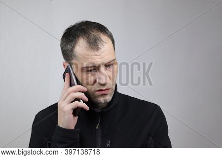 A Young Caucasian Man Is Having An Unpleasant Conversation On A Smartphone.