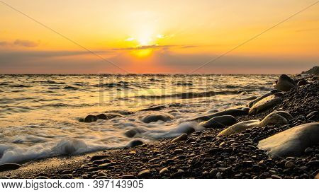 Sunset At The Sea. Pebble Beach And Surf At Sunset. Long Exposure Shooting. Focusing On Water's Edge