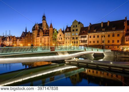 Footbridge Over The Motlawa River And Historic Architecture Of Gdansk Old Town At Night. Poland