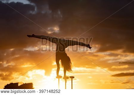 Flexible Acrobat Doing Handstand On The Cityscape Background During Dramatic Sunset. Concept Of Will
