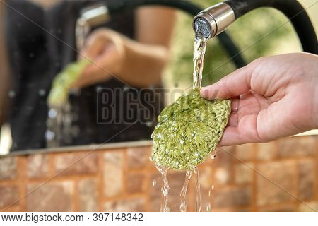 Close Up Of A Hand Washing Reusable Crocheted Pad Under Running Tap Water. Diy Washable Knitted Make