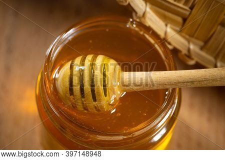 Honey In A Glass Jar With A Wooden Honey Dipper On A Wooden Table. Healthy Organic Honey. Close-up