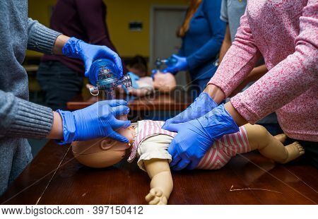 Newborn Resuscitation On A Infant Dummy Doll. First Help Medical Class.