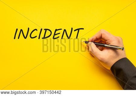 Male Hand Writes In Black Pen The Word Incident On A Yellow Background With Copy Space. Business Con