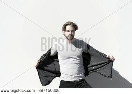 Guy Take Off Warm Coat On Sunny Day On Grey Wall. Fashion, Sport Style, Sportswear. Heat, Warmth, En