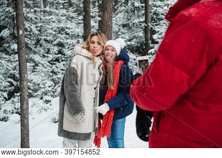 Mom And Daughter Pose For Dad During A Weekend Trip To The Woods During The Christmas Holidays.