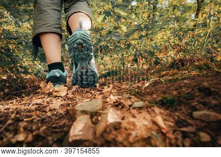 Hiker Boots Footsteps On Muddy Ground. Sole Of Shoe In Motion On Track. Walking Hike. Close-up Of Wo