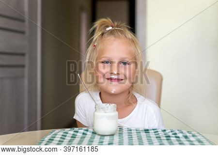 Cute Adorable Caucasian Little Funny Blond Girl Eating Yogurt Or Milk Cottage Cheese For Lunch Snack