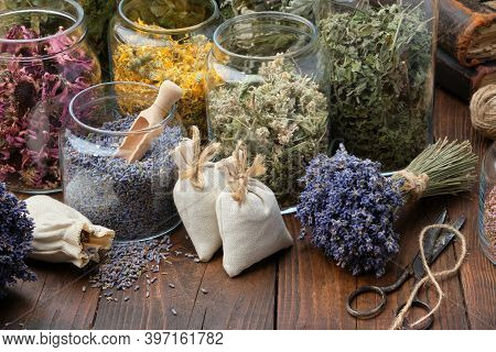 Glass Jars Of Dry Different Medicinal Herbs, Aromatic Sachets, Bunches Of Dry Lavender On Table. Alt