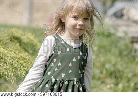 Cute Blond Hair Little Girl In Dress Is Outdoors.