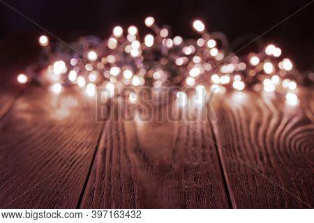 Blured Shining Christmas Lights Garland On A Dark Wood Tabletop. Glowing Led Lightning Decorations I