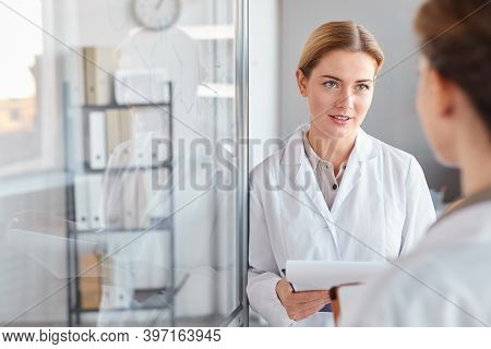 Waist Up Portrait Of Two Female Scientists Talking And Holding Clipboard While Doing Research In Med