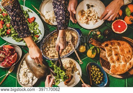 Family Having Turkish Dinner. Flat-lay Of People Hands Taking Lamb In Yogurt Sauce, Arugula And Stra