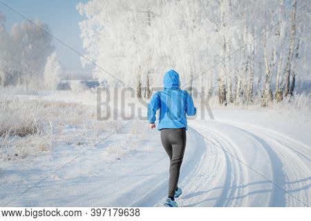Fitness Woman Runner Running On Sunny Winter Road. Running Sport Woman. Change In Life.