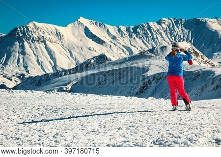 Sporty Skier Woman Taking A Picture With Phone From The Snowy Mountains And Winter Ski Resort. Happy