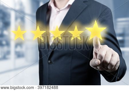 Businessman Hand Touching Five Star Symbol. Man Is Pointing Five Stars - Review And Rating Concept.