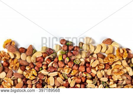 Nuts, Overhead Shot On A White Background With Copy Space. A Mix Of Peanuts, Hazelnuts, Walnuts, Pis
