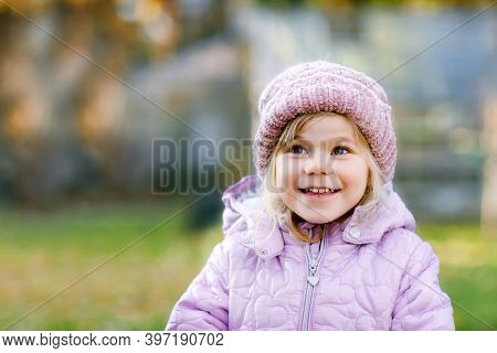 Portrait Of Adorable Cute Toddler Girl Of Three Years. Beautiful Baby With Blond Hairs Looking And S