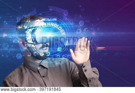 Businessman looking through Virtual Reality glasses with BIOTECHNOLOGY inscription, innovative technology concept