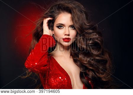 Beautiful Sexy Brunette In Red Dress With Healthy Curly Hair And Glamour Makeup. Fashion Beauty Girl