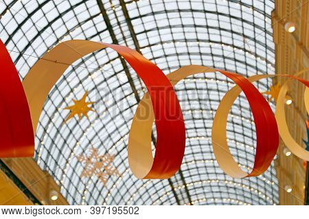 Christmas Decorations Under The Glass Roof Of The Store. Serpentine Ribbon, New Year Celebration