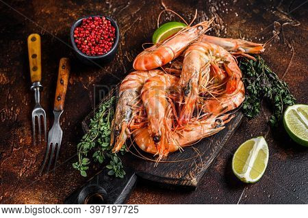 Giant Tiger Prawns Shrimps On A Cutting Board With Herbs. Dark Background. Top View