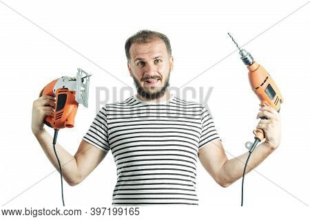 A Stupid Man Holds A Drill And An Electric Jigsaw In His Hands. How To Choose A Power Tool