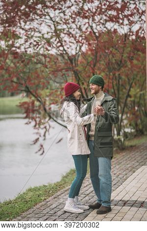 Couple Hugging Near The River While Walking