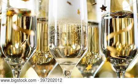 Champagne Flutes with Bubbles on Golden Light Background, Close-up.