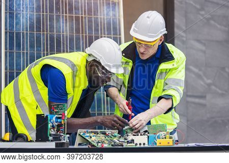 Engineer Working Repairing Electric Panel With Solar Panels Background, Concept Teamwork Or Training