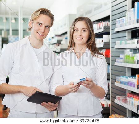 Portrait of happy young pharmacists with digital tablet in pharmacy
