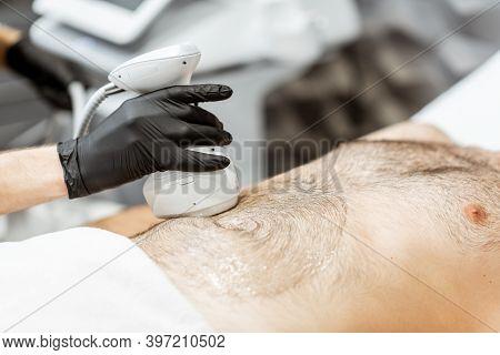 Man During An Ultrasound Liposuction Procedure At Luxury Spa Salon. Doctor Working On Abdomen Area,