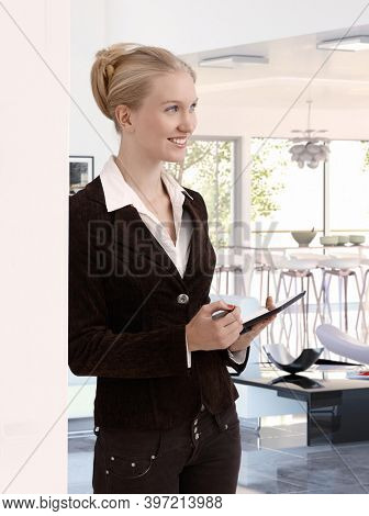 Tall attractive blonde caucasian businesswoman with tablet at home. Standing, smiling, leaning against wall.