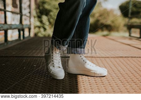High top white sneakers on jeans model