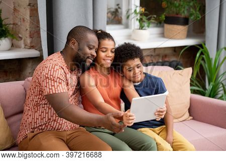 Happy African family of father, son and daughter with digital tablet sitting on couch in living-room and watching movie while staying at home