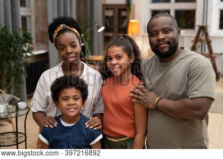Happy young African husband and wife and their affectionate son and daughter standing close to each other in front of camera at home
