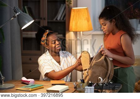 Happy young African female in casualwear helping her teenage daughter with packing backpack for school in the morning while sitting by table