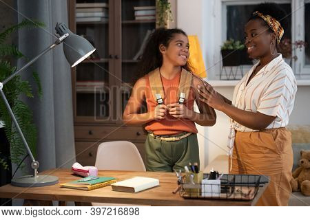 Happy young African female in casualwear blessing her teenage daughter with backpack before school in the morning while looking at her